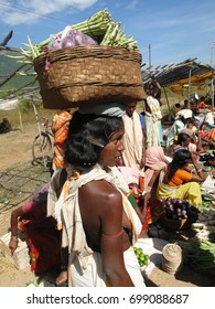 ORISSA,  INDIA - NOV 11, 2009 - Tribal women carry goods  on their headsIndia