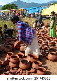 ORISSA, INDIA - NOV 11 - Tribal women buy clay pots    on Nov 11, 2009,  in Chatikona market, Orissa, India