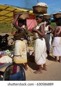 ORISSA,  INDIA - Nov 11 -Tribal women carry goods  on their heads on Nov 11, 2009 in Ankadeli, Orissa in India