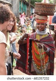 ORISSA,  INDIA - NOV 12, 2009 - Bonda tribal women offer their handmade crafts to western tourists at the weekly market  in Ankadeli, Orissa in India