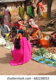 ORISSA,  INDIA - NOV 12, 2009 - Tribal women sell vegetables  in  weekly market  in Ankadeli, Orissa in India