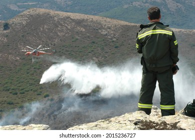 Oristano, Italy - July 25 2021: a renger communicates with the crew of a Sikorsky S-64 Skycrane (blurred in the background) during a firefighting mission.