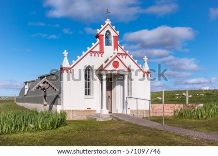Orkneys, Scotland - June 5, 2012: The entire building, entrance and front facade of the white and maroon painted Italian Chapel on Lamb Holm Island. Green lawn in front, against deep blue sky.