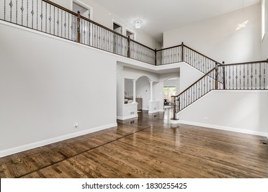ORLAND PARK, IL, USA - MAY 20, 2019: A large, empty living area with a large staircase leading to the second floor. The staircase features wood rails and wrought iron spindles.