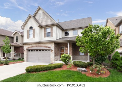 ORLAND PARK, IL, USA - MAY 20, 2019: A new suburban house with half light brown siding and have brick and stone, brown window shutters, and a front porch.