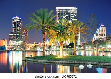 Orlando downtown skyline panorama over Lake Eola at night with urban skyscrapers, tropic palm tree and clear sky.