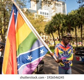 Orlando, FL - February 28, 2021: A  man carrying a gay pride Confederate flag shows his support for ex-president Trump outside the CPAC at the Hyatt Regency hotel.
