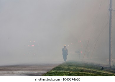 Orlando, FL. March 2018 - A Florida Forestry Service Firefighter walks through the smoke of a 4-acre forest fire in Orange County's Wedgefield Subdivision. The flashing vehicle lights can be seen.