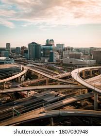 """Orlando, FL / USA - 08-31-2020: Sunrise vertical shot of downtown Orlando skyline over the I-4 and 408 expressway interchange."""