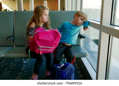 Orlando, FL, USA - 12/22/17: Bored children waiting in an airport for a delayed flight