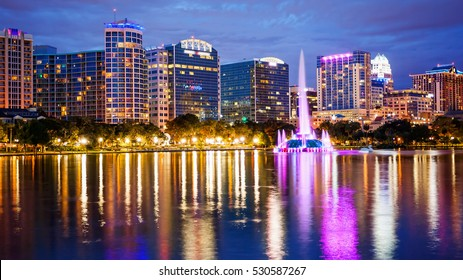 Orlando, Florida city skyline and water fountain at night in Lake Eola Park, building logos blurred for commercial use)