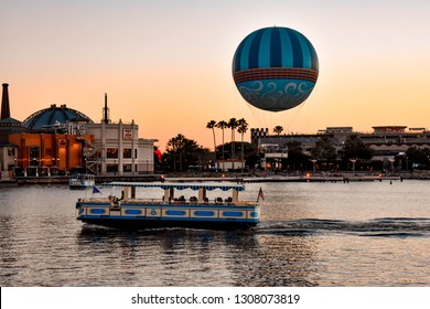 Orlando, Florida. January 11, 2019 Panoramic view  of Disney Springs and water taxi on colorful sunset background at Lake Buena Vista area  (1)
