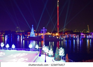 Orlando, Florida. November 21, 2018. Ice skating scene , colorful holidays trees and Christmas Tree on lake and Sky Tower background in International Drive area