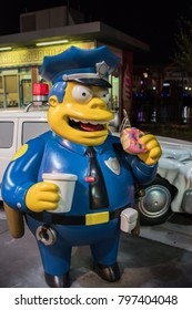 Orlando, Florida: November 30, 2017:  The Simpsons area at Universal Studios Florida.  Chief Wiggum and police car statue with a doughnut shop in the background.
