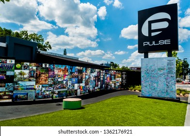 Orlando, Florida / United States - June 19, 2018 : Pulse Nightclub Interim Memorial south side Pulse sign and visitor message board, east wall photographs, and lawn
