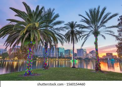 Orlando, Florida, USA downtown skyline at Eola Lake at dusk.