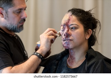 Orlando, Florida / USA - September 15, 2018: Special Effects Makeup Artist with a Female Model with Body Paint and Mask at The Makeup Show in Orlando, FL