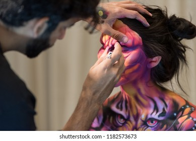 Orlando, Florida / USA - September 15, 2018: Special Effects Makeup Artist with a Female Model with Tiger Body Paint and Mask at The Makeup Show in Orlando, FL