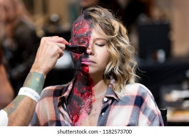 Orlando, Florida / USA - September 15, 2018: Special Effects Makeup Artist with a Female Model with Body Paint at The Makeup Show in Orlando, FL