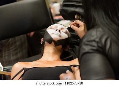 Orlando, Florida / USA - September 15, 2018: Makeup Artist Applying Creative Cosmetics to a Female Model Lying Down at The Makeup Show in Orlando, FL