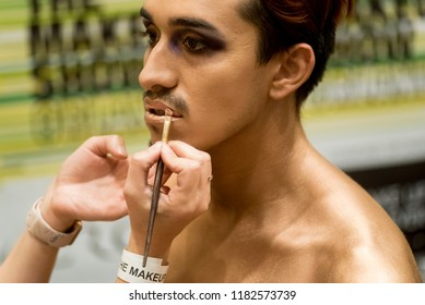 Orlando, Florida / USA - September 15, 2018: Male Model Having Gold Colored Lipstick and Cosmetics Applied by a Makeup Artist at The Makeup Show in Orlando, FL