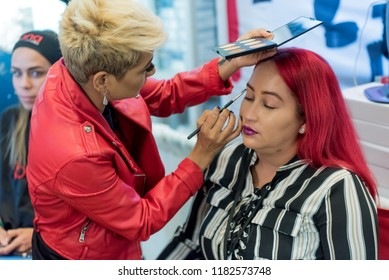 Orlando, Florida / USA - September 15, 2018: Woman with Red Hair, Having Cosmetics Applied by a Makeup Artist at The Makeup Show in Orlando, FL