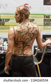 Orlando, Florida / USA - September 15, 2018: Male Model with Gold Body Paint Design at The Makeup Show in Orlando, FL