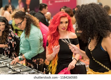 Orlando, Florida / USA - September 15, 2018: Attractive Woman with Red Hair Talking to Her Friend at The Makeup Show in Orlando, FL