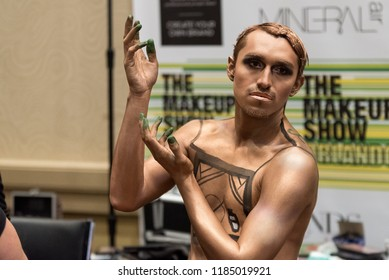 Orlando, Florida / USA - September 15, 2018: Male Model Posing with Gold Body Paint Cosmetics at The Makeup Show in Orlando, FL