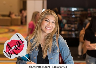 Orlando, Florida / USA - September 15, 2018: Pretty Young Woman with a Big Smile Holding a Sign at The Makeup Show in Orlando, FL
