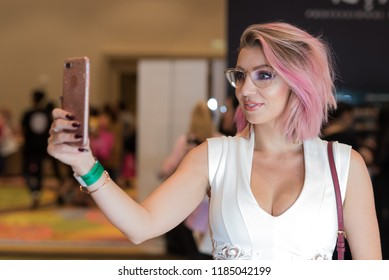 Orlando, Florida / USA - September 15, 2018: Attractive  Woman with a Lovely Smile Taking a Selfie with Her Mobile Phone  at The Makeup Show in Orlando, FL