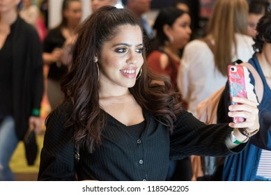Orlando, Florida / USA - September 15, 2018: Attractive Young Woman Taking a Selfie with Her Phone  at The Makeup Show in Orlando, FL