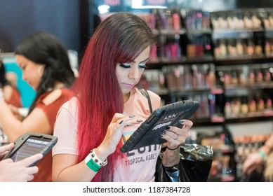 Orlando, Florida / USA - September 15, 2018: Attractive Woman Making a Purchase on a Tablet at The Makeup Show in Orlando, FL