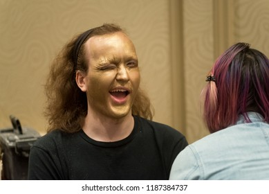 Orlando, Florida / USA - September 15, 2018: Male Model in Gold Makeup Winking Eye at The Makeup Show in Orlando, FL