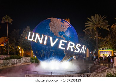 Orlando, Florida, USA-July 7,2019: The Universal Studios logo rotating at night at the entrance of one of the themed parks in the area. The place is a famous tourist attraction in Florida.