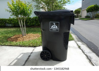 Orlando, FL/United States - 03/20/19:  Full garbage bin waiting for the garbage truck to collect the garbage.