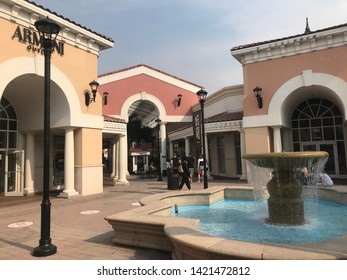 Orlando, USA, June 12, 2019: Kate Spade, renowned brand store, modern outlet, beautiful architectural designs, classic colors, some people near a fountain.