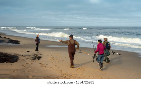 Orleans, MA - October 29,2019: Two men and one woman wearing cold weather gear carry fishing poles as they walk along Nauset Beach on an ocean fishing outing