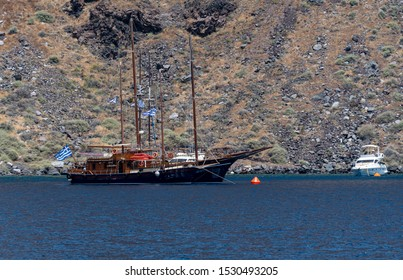 Ormos Korfou, Greece - July 16 2019:   A tourist boat and a cabin cruiser anchored in the waters of the Aegean Sea off Ormos Korfou