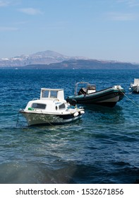 Ormos Korfou, Greece - July 16 2019:   Two boats, a dinghy and  a small cabin cruiser, tied up in the waters of the Aegean Sea at the dock of Ormos Korfou