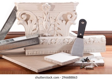 Ornament of plaster, dry wall, trowel, screws, dowels and parquet