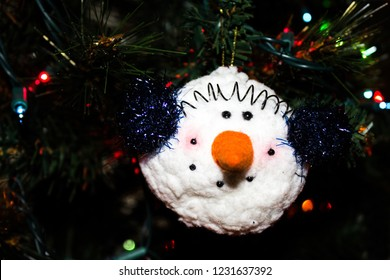 Ornament of a Snowman with a Carrot Nose and Wearing Ear Muffs hanging on a Christmas Tree