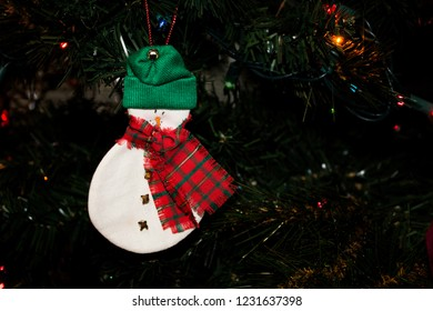 Ornament of a Snowman with a Carrot Nose and Wearing a Stocking Cap hanging on a Christmas Tree