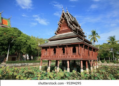 Ornament: traditional wooden chedi on the lotus pond against blue sky at wat Thung Si Muang in Ubon Ratchathani province, Thailand