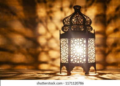 Ornamental Arabic lantern with burning candle glowing