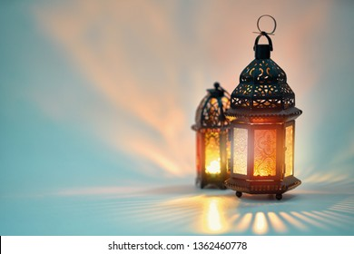Ornamental Arabic lantern with burning candle glowing on white background. Festive greeting card, invitation for Muslim holy month Ramadan Kareem.