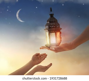 Ornamental Arabic lantern with burning candle glowing in hand. Festive greeting card, invitation for Muslim holy month Ramadan Kareem.