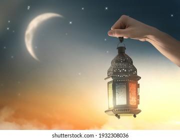 Ornamental Arabic lantern with burning candle glowing in hand. Festive greeting card, invitation for Muslim holy month Ramadan Kareem. - Shutterstock ID 1932308036