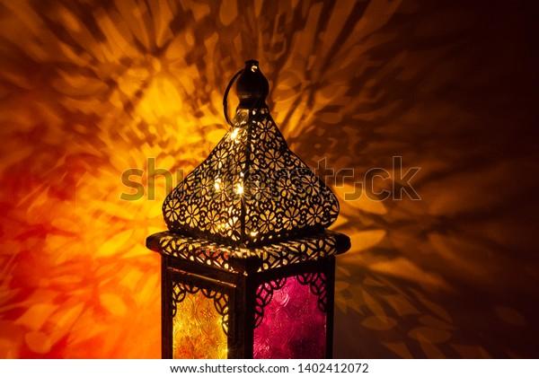 Ornamental Arabic lantern with burning light glowing at night and glittering golden bokeh lights. Festive greeting card, invitation for Muslim holy month Ramadan Kareem. Dark background. - Image
