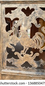 Ornamental art deco style gratings with rooster cutout silhouette. Decorative elements of aged metal gates. Cutout ornaments. Grunge textures. Pattern of cock bird side view with blurred background